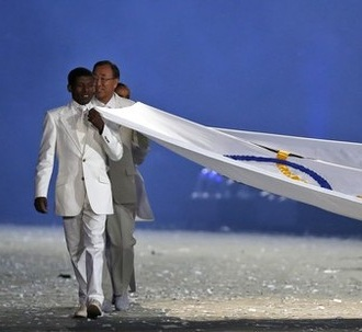 Haile Gebrselassie takes the honor of carrying the Olympic flag